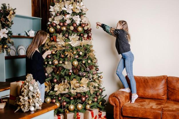 Mutter und tochter schmücken einen weihnachtsbaum im wohnzimmer.