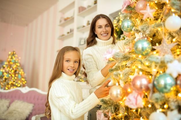 Mutter und tochter schmücken gemeinsam den weihnachtsbaum und fühlen sich gut