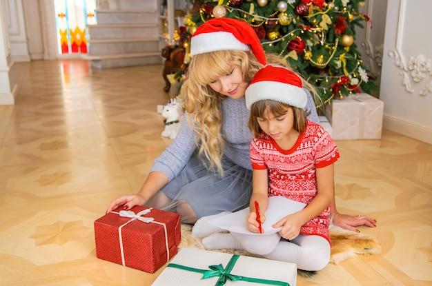 Mutter und tochter schreiben einen brief an den weihnachtsmann. tiefenschärfe.
