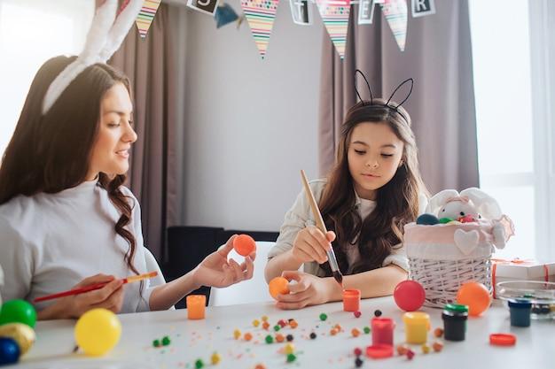 Mutter und tochter sitzen am tisch und bereiten sich auf ostern vor. sie malen eier. mädchen erreichen farbe mit pinsel. junge frau halten orange ei.
