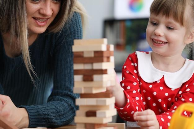 Mutter und tochter sitzen am tisch und spielen ein spiel