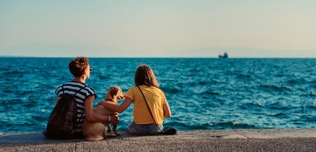 Mutter und tochter sitzen am wasser mit hund