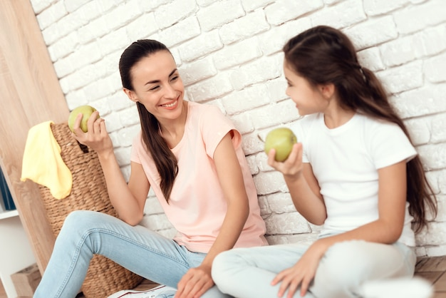 Mutter und tochter sitzen auf dem boden und essen einen apfel.