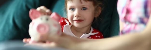 Mutter und tochter sitzen auf dem grünen sofa und spielen. frau halten rosa sparschwein in ihrer hand. freudiges kind legte münze in sparbüchse.