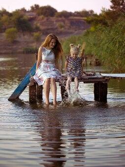 Mutter und tochter sitzen auf dem pier