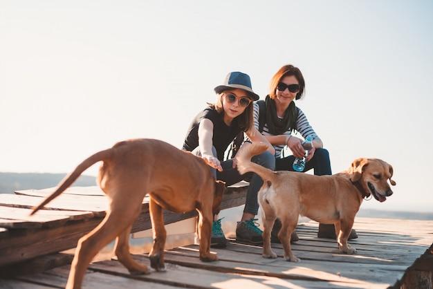 Mutter und tochter sitzen auf einem holzdeck mit zwei hunden