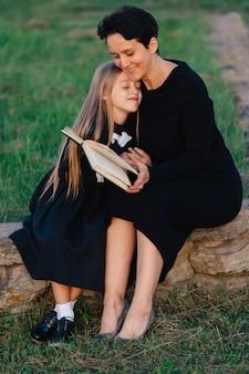 Mutter und tochter sitzen auf einer steinbank und lesen ein buch. frau mit einem kind in schwarzen kleidern.