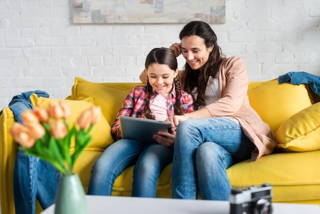 Mutter und tochter sitzen auf gelber couch vorderansicht