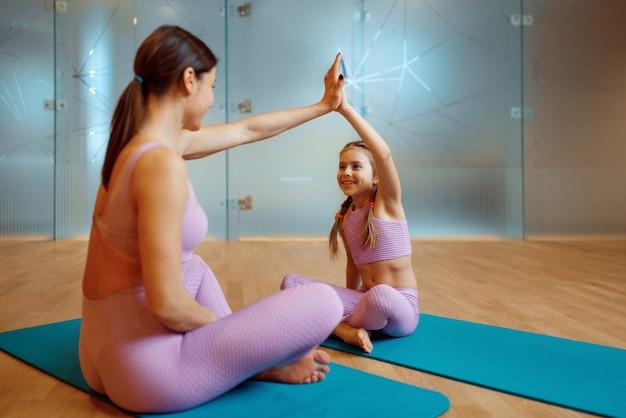 Mutter und tochter sitzen auf matten im fitnessstudio, yoga-training. mutter und kleines mädchen in sportkleidung, gemeinsames training im sportclub