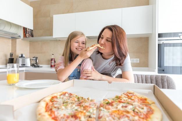 Mutter und tochter sitzen in der küche, essen pizza und haben spaß