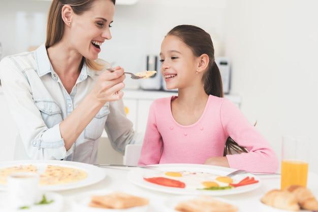 Mutter und tochter sitzen in der küche und essen.