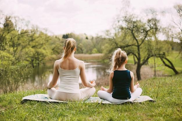 Mutter und tochter sitzen in der lotus-position im garten