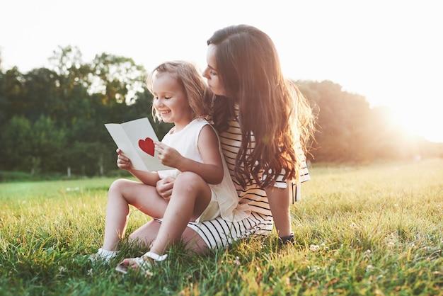 Mutter und tochter sitzen und lesen das kleine buch mit herz auf dem cover