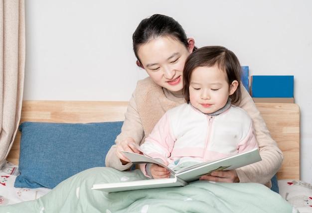 Mutter und tochter sitzen zusammen auf dem bett und lesen