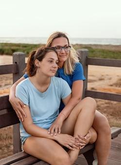 Mutter und tochter sitzen zusammen auf einer holzbank bei sonnenuntergang. lächelnde frau mittleren alters, die teenager-soulders umarmt. t-shirt-modell