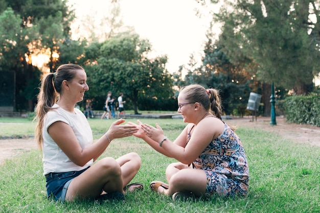 Mutter und tochter sitzen zusammen und haben spaß in einem park.