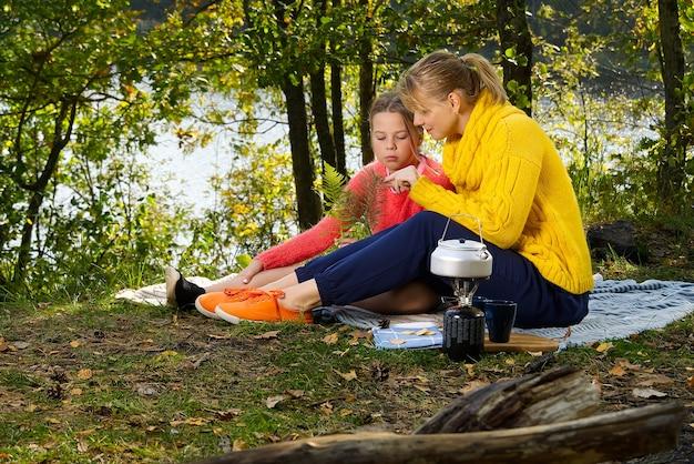 Mutter und tochter spielen auf einer decke im herbstwald in der nähe des flusses oder sees. junge mutter, die mit ihrer tochter im herbstpark am sonnigen tag spielt