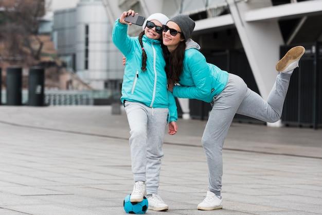 Mutter und tochter spielen mit ball und machen selfie