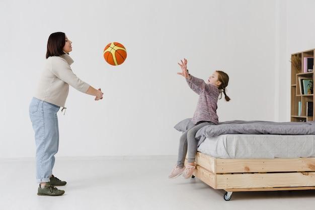 Mutter und tochter spielen mit basketball
