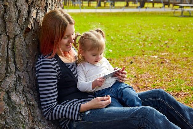 Mutter und tochter spielen mit dem smartphone