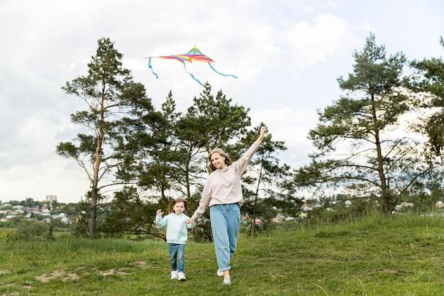 Mutter und tochter spielen mit drachen