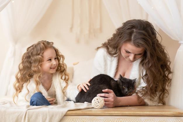 Mutter und tochter spielen mit grauer rauchiger britischer katze