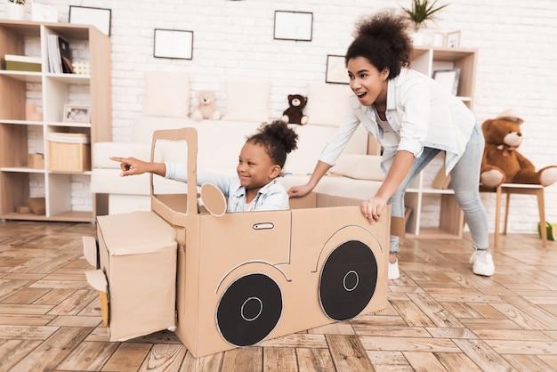 Mutter und tochter spielen mit großen spielzeugautos.