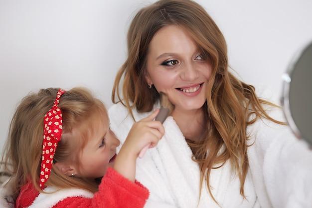 Mutter und tochter spielen mit make-up