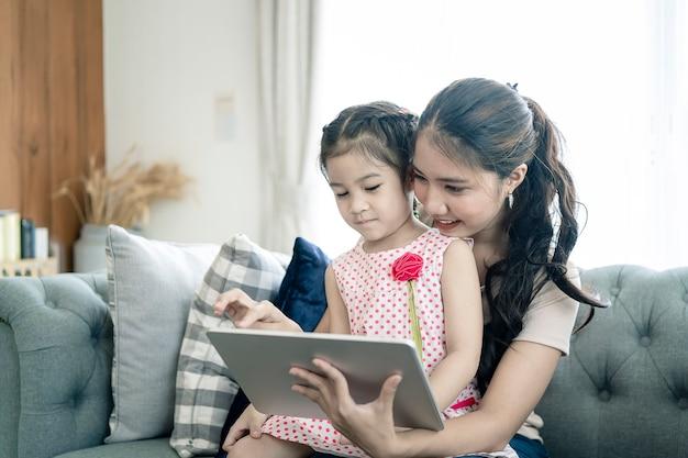 Mutter und tochter spielen zu hause mit tablet-computer