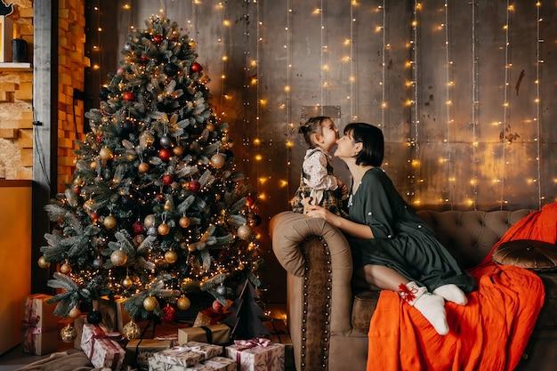 Mutter und tochter spielen zu hause neben einem weihnachtsbaum und sitzen auf einem sofa