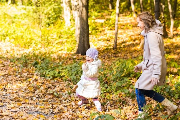 Mutter und tochter spielen zusammen im herbstpark. Premium Fotos