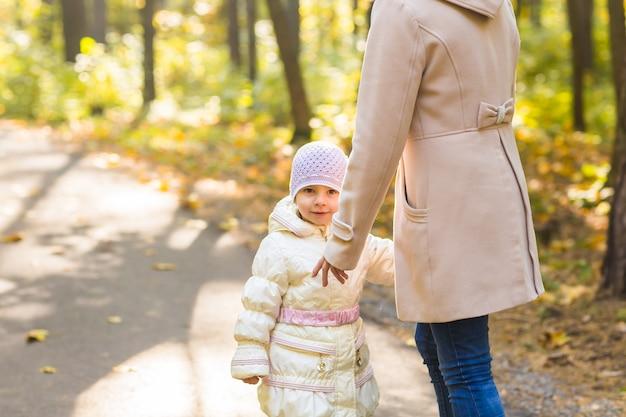 Mutter und tochter spielen zusammen im herbstpark.