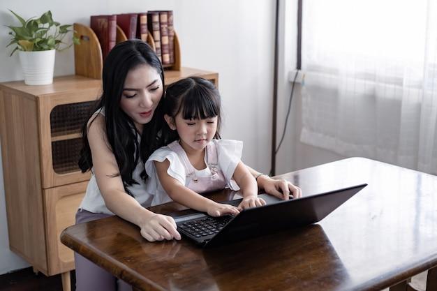 Mutter und tochter spielen zusammen laptop im wohnzimmer zu hause.