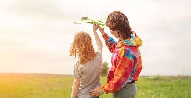 Mutter und tochter starten spielzeugflugzeug auf dem feld bei sommermädchen und -frau