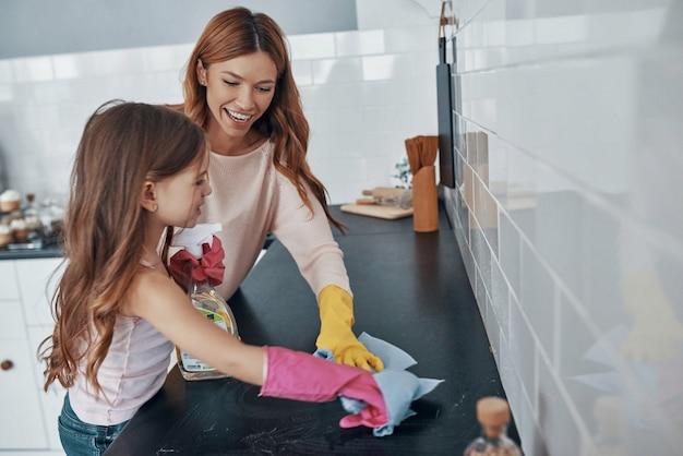 Mutter und tochter stauben mit abwaschhandschuhen ab, während sie zeit zu hause verbringen