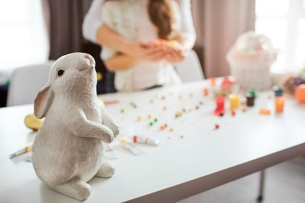 Mutter und tochter stehen im zimmer und bereiten sich auf ostern vor. weißes häschenspielzeug stehen auf tisch. dekoration und süßigkeiten dahinter. festlich. nahansicht.