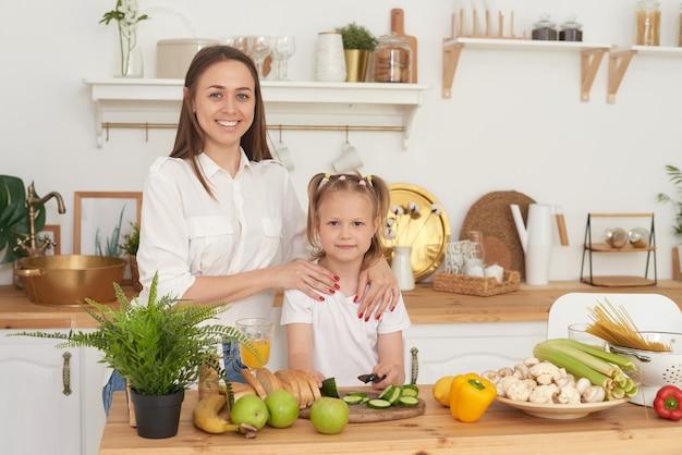 Mutter und tochter stehen in der küche des hauses, schauen in die kamera und lachen.