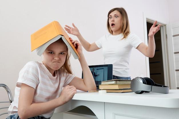 Mutter und tochter streiten sich um hausaufgaben, verärgerte mutter ist wütend auf kleine gelangweilte tochter, homeschooling, missverständnisse