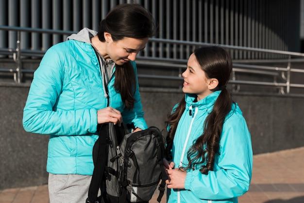 Mutter und tochter suchen etwas in einem rucksack