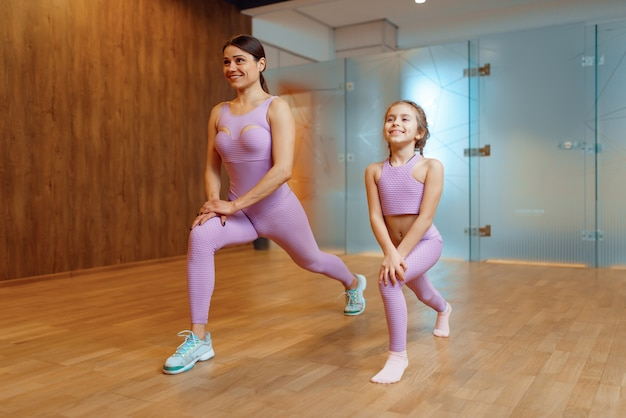 Mutter und tochter trainieren im fitnessstudio, fitnesstraining. mutter und kleines mädchen in sportkleidung, gemeinsames training im sportclub