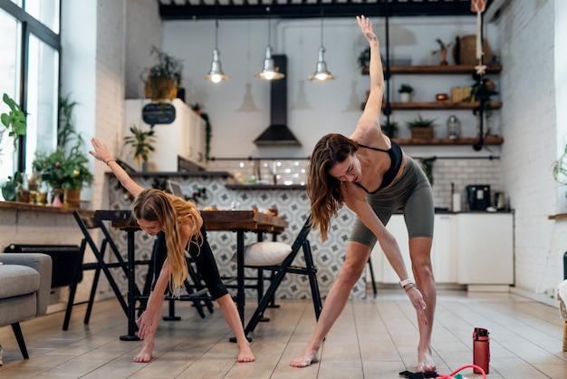 Mutter und tochter trainieren zu hause und machen stehende crossover-zehenberührungen.