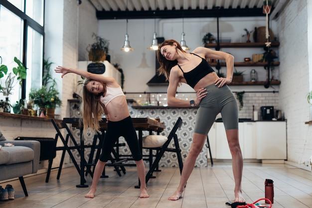 Mutter und tochter trainieren zu hause und machen stehende kurven zu den seiten.