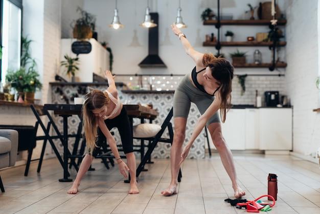 Mutter und tochter treiben zu hause sport, machen stehbeugen bis zu den zehen, verdrehen den rücken.