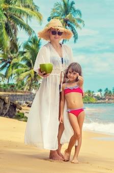 Mutter und tochter trinken kokosnuss am strand