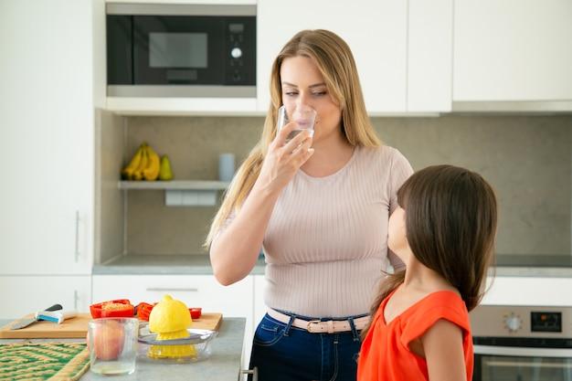 Mutter und tochter trinken wasser, während sie zitronensaft auspressen und salat zusammen in der küche kochen. familienkochen oder gesundes lebensstilkonzept