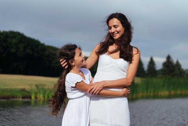 Mutter und tochter umarmen am see