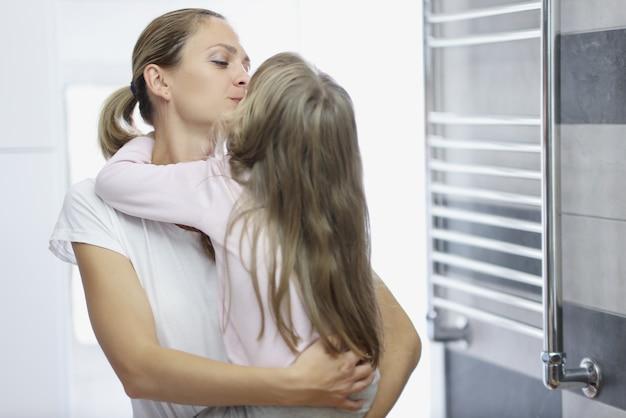 Mutter und tochter umarmen sich am frühen morgen