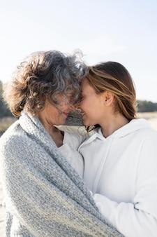 Mutter und tochter umarmen sich draußen am strand