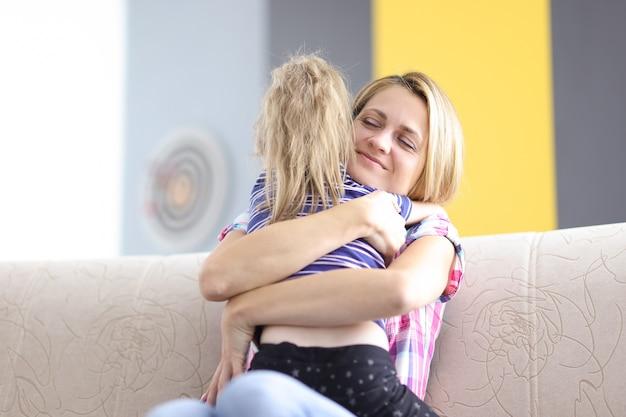 Mutter und tochter umarmen sich fest auf der couch