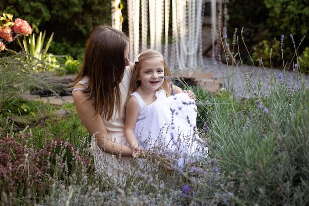 Mutter und tochter umarmen sich im lavendel und haben spaß im freien in der natur